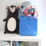 Blue Temptationless Bank on shelf beside stuffed bear