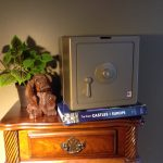 Gold Temptationless Bank beside plant on nightstand